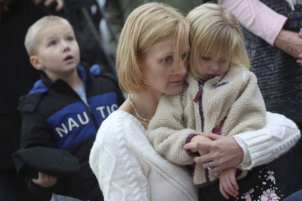 Barbara Wells of Shelton, Conn., holds her daughter Olivia, 3, as she pays her respects Monday, Dec. 17, 2012 at one of the makeshift memorials for the victims of the Sandy Hook Elementary School shooting in Newtown, Conn. (AP Photo/Mary Altaffer) ORG XMIT: CTMA103