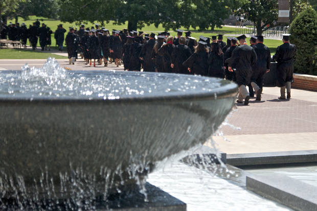 The College of Education graduates walk past the Edmon Low library fountain before the Oklahoma State University graduation held in Gallagher Iba Arena in Stillwater, Oklahoma on May 5th, 2012. Photos by Mitchell Alcala for the Oklahoman
