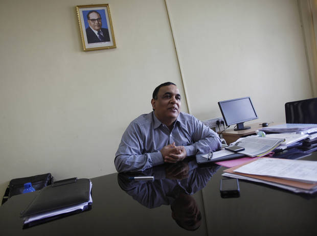 In this Dec. 3, 2012 photo, a portrait of Bhimrao Ramji Ambedkar, a dalit leader and architect of the Indian Constitution, hangs on the wall as Rajeev Chawla, the government administrator who created Bhoomi, a program that digitized Karnataka state's 20 million handwritten land records, speaks to The Associated Press at his office in Bangalore, India. For years, Karnataka's land records were a quagmire of disputed, forged documents maintained by thousands of tyrannical bureaucrats who demanded bribes to do their jobs. In 2002, there were hopes that this was about to change. (AP Photo/Aijaz Rahi)
