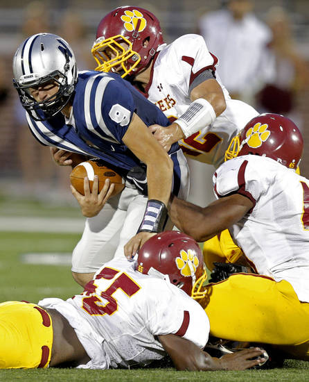 Edmond North's Luke Hoskins is brought down by Putnam City North's Ruben Hunter, top, Eric Sadler, and Wendell Mickel , bottom, during a high school football game at Wantland Stadium in Edmond, Okla., Friday, September 21, 2012. Photo by Bryan Terry, The Oklahoman