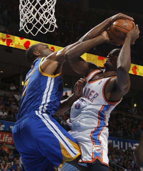 Oklahoma City 's Serge Ibaka (9) goes against Golden State's Carl Landry (7) during an NBA basketball game between the Oklahoma City Thunder and the Golden State Warriors at Chesapeake Energy Arena in Oklahoma City, Sunday, Nov. 18, 2012.  Photo by Garett Fisbeck, The Oklahoman