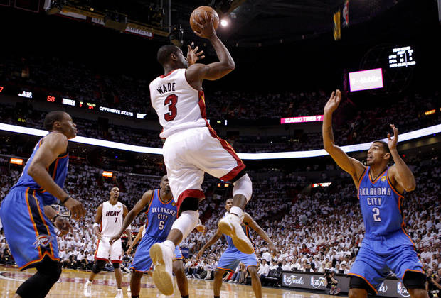 Miami's Dwyane Wade (3) shoots the ball as Oklahoma City's Thabo Sefolosha (2) and Russell Westbrook (0) defend during Game 5 of the NBA Finals between the Oklahoma City Thunder and the Miami Heat at American Airlines Arena, Thursday, June 21, 2012. Photo by Bryan Terry, The Oklahoman