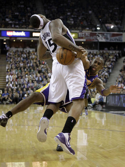 Sacramento Kings center DeMarcus Cousins, left, is fouled by Los Angeles Lakers guard Jodie Meeks, right, during the fourth quarter of an NBA basketball game in Sacramento, Calif., Saturday, March 30, 2013.  The Lakers won 103-98.(AP Photo/Rich Pedroncelli)