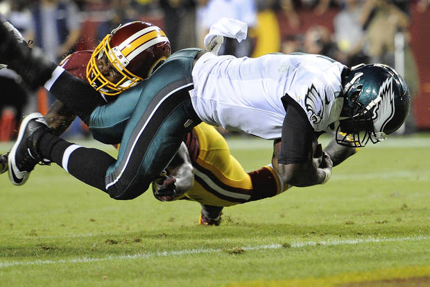 Philadelphia Eagles quarterback Michael Vick, right, scores a touchdown on the quarterback keeper under pressure from Washington Redskins strong safety Bacarri Rambo during the first half of an NFL football game in Landover, Md., Monday, Sept. 9, 2013. (AP Photo/Nick Wass)
