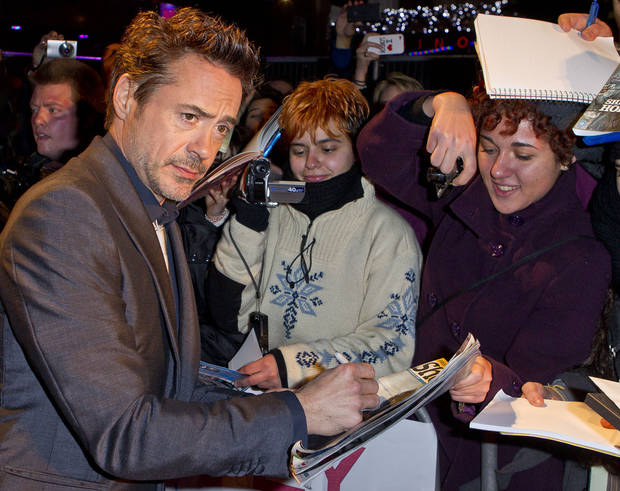 Actor Robert Downey Jr. signs autographs as he arrives on the red carpet for the European Premiere of Sherlock Holmes: A Game of Shadows, a filmed directed by Guy Ritchie, at a central London cinema, London, Thursday, Dec. 8, 2011. (AP Photo/Joel Ryan) ORG XMIT: LENT119