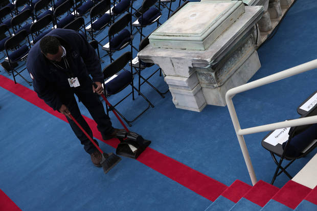 An usher prepares the seating area on the West Front of the Capitol in Washington, Monday, Jan. 21, 2013, before the start of President Barack ceremonial swearing-in ceremony during the 57th Presidential Inauguration. (AP Photo/Win McNamee, Pool)