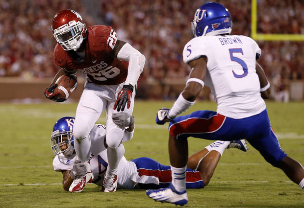 OU's Damien Williams (26) tries to get past KU's Bradley McDougald (24) and Greg Brown (5) during the college football game between the University of Oklahoma Sooners (OU) and the Kansas Jayhawks (KU) at Gaylord Family-Oklahoma Memorial Stadium in Norman, Okla., Saturday, Oct. 20, 2012. Photo by Bryan Terry, The Oklahoman