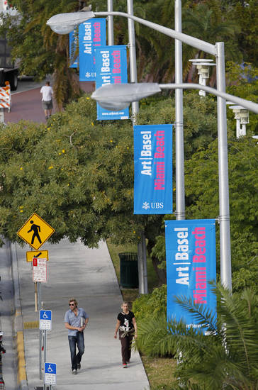 Pedestrians walk under banners announcing Art Basel Miami Beach, Tuesday, Dec. 4, 2012 in Miami Beach, Fla. Art Basel Miami Beach and about two dozen other independent art fairs open Thursday. Tens of thousands of people are expected through Sunday at the fairs throughout Miami and South Beach. (AP Photo/Wilfredo Lee)