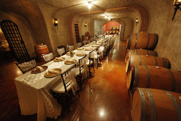 Wine barrels line the wall inside the wine cave at Clauren Ridge Vineyard and Winery. The room is used for wine tastings and wedding receptions. <strong>STEVE GOOCH - THE OKLAHOMAN</strong>