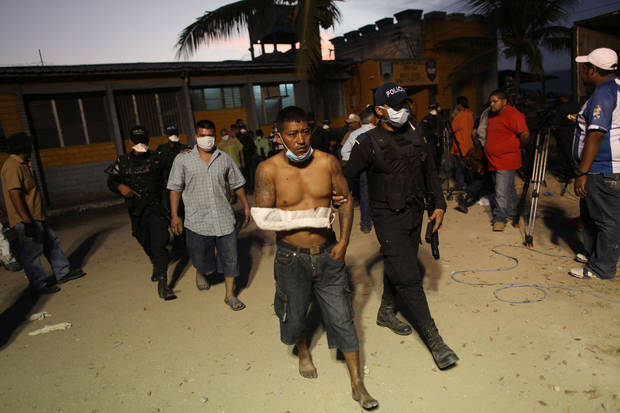 Police officers escort surviving inmates from the prison in Comayagua, Honduras, Wednesday Feb. 15, 2012. A fire started by a prisoner late Tuesday tore through the prison killing 358 inmates, said Supreme Court Justice Richard Ordonez, who is leading the investigation. (AP Photo/Esteban Felix)