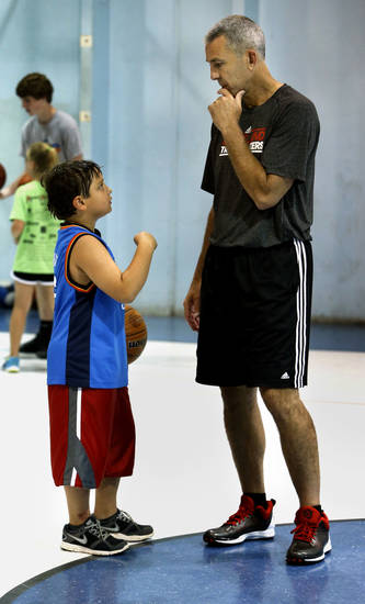 Former professional basketball player John McCullough answers a question from Ismael Marakah, 8, at a city-sponsored basketball camp this week at Whittier Recreation Center. PHOTO BY STEVE SISNEY, THE OKLAHOMAN <strong>STEVE SISNEY</strong>
