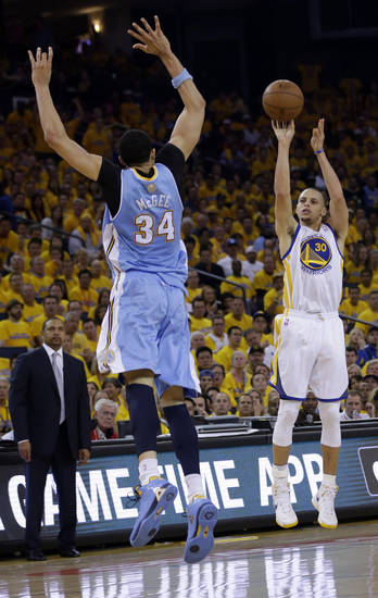 Golden State Warriors' Stephen Curry (30) shoots over Denver Nuggets' JaVale McGee (34) during the first half of Game 6 in a first-round NBA basketball playoff series in Oakland, Calif., Thursday, May 2, 2013. (AP Photo/Marcio Jose Sanchez)