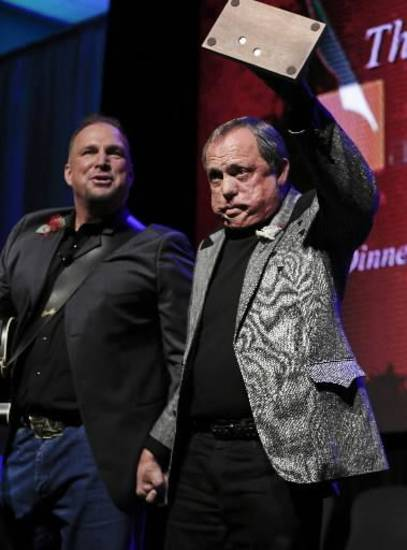 Kim Williams acknowledges the audience as he is inducted into the Nashville Songwriters Hall of Fame on Sunday, Oct. 7, 2012, in Nashville, Tenn. Garth Brooks watches at left.