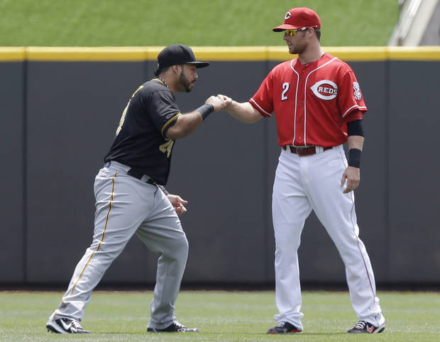 Cincinnati Reds shortstop Zack Cozart (2) bumps fists with Pittsburgh Pirates third baseman Pedro Alvarez as they warm up before a baseball game on Sunday, July 21, 2013, in Cincinnati. (AP Photo/Al Behrman)