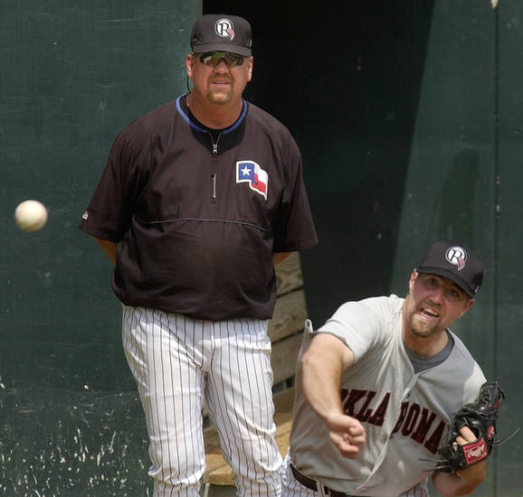 Oklahoma City - June 20, 2003.   MINOR LEAGUE BASEBALL: R.A. Dickey pitches in the bullpen after reporting to the Oklahoma RedHawks as pitching coach Glen Abbott watches. Dickey was recently sent down from the Texas Rangers baseball team. Staff photo by Nate Billings.