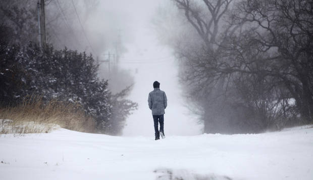 A man walks through deep snow on E Charter Oak Road in Logan County, Oklahoma February 1, 2011. Photo by Steve Gooch, The Oklahoman