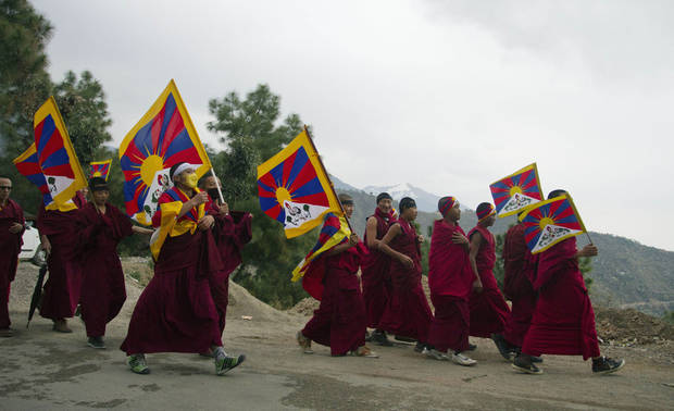 Exiled Tibetan Buddhist monks carrying Tibetan flags walk during a protest march in Dharmsala, India, as they mark the anniversary of a failed 1959 uprising against Chinese rule, Sunday, March 10, 2013. Police in India prevented a Tibetan man from setting himself on fire as hundreds of Tibetan exiles gathered to mark the anniversary in Dharmsala, the home of Tibet's government in exile. (AP Photo/ Ashwini Bhatia)