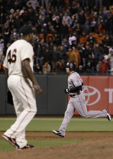 Colorado Rockies' Marco Scutaro, rear, rounds the bases after hitting a solo home run off of San Francisco Giants pitcher Santiago Casilla (46) during the ninth inning of a baseball game in San Francisco, Tuesday, May 15, 2012. (AP Photo/Jeff Chiu)