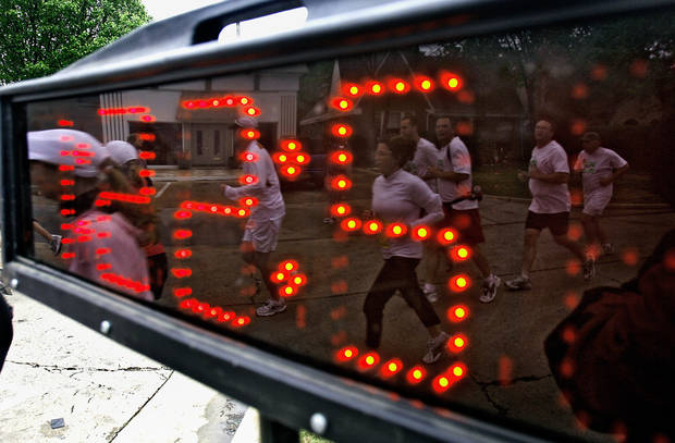 Marathon runners are reflected in the official course timer during the eighth annual Oklahoma City Memorial Marathon on Sunday , April 27, 2008, in Oklahoma City, Okla.   PHOTO BY CHRIS LANDSBERGER   ORG XMIT: KOD
