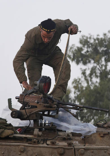An Israeli soldier loads ammunition into a weapon atop a tank at a staging area near the Israel Gaza Strip Border, southern Israel, Tuesday, Nov. 20, 2012. On Tuesday, grieving Gazans were burying militants and civilians killed in ongoing Israeli airstrikes, and barrages of rockets from Gaza sent terrified Israelis scurrying to take cover. Efforts to end a week-old convulsion of Israeli-Palestinian violence drew in the world's top diplomats Tuesday, with U.S. President Barack Obama dispatching his secretary of state to the region on an emergency mission and the U.N. chief appealing from Cairo for an immediate cease-fire. (AP Photo/Lefteris Pitarakis)
