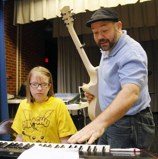 The Rev. Ernie Tullis, pastor of Tri-Church, teaches Danielle Mader, 10, to play piano at Mark Twain Elementary School, where Tullis' church holds Sunday services. Photo by Jim Beckel, The Oklahoman   <strong>PAUL HELLSTERN</strong>