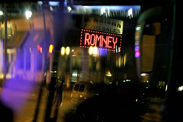 A sign supporting Republican presidential candidate, former Massachusetts Gov. Mitt Romney, appears at an auto sales store as Romney's motorcade passes through the street en route to a campaign event at the Verizon Wireless Arena, Monday, Nov. 5, 2012, in Manchester, N.H. (AP Photo/David Goldman)