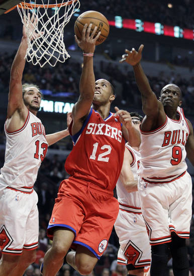 Philadelphia 76ers forward Evan Turner, center, shoots against Chicago Bulls center Joakim Noah (13) and forward Luol Deng during the first half of an NBA basketball game in Chicago on Saturday, Dec. 1, 2012. (AP Photo/Nam Y. Huh)