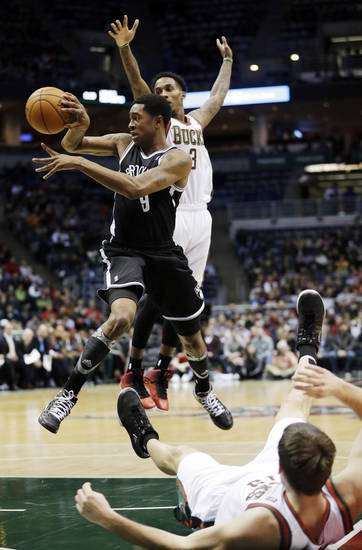 Brooklyn Nets' MarShon Brooks (9) looks to pass between Milwaukee Bucks' Brandon Jennings (3) and Beno Udrih during the first half of an NBA basketball game, Wednesday, Dec. 26, 2012, in Milwaukee. (AP Photo/Morry Gash)