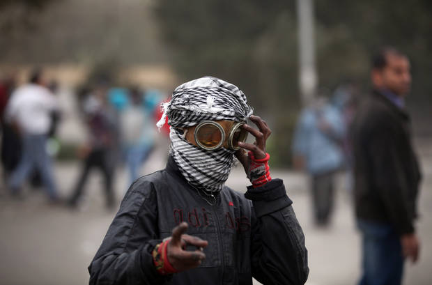 An Egyptian protester covers his face during clashes with riot police, not seen, near Tahrir Square, Cairo, Egypt, Monday, Jan. 28, 2013. Health and security officials say a protester has been killed in clashes between rock-throwing demonstrators and police near Tahrir Square in central Cairo. The officials say the protester died Monday on the way to the hospital after being shot. (AP Photo/Khalil Hamra)