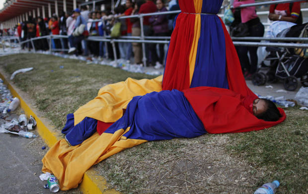 A woman wrapped in cloths decorating a light post in the colors of Venezuela's flag sleeps outside the military academy where a funeral ceremony will take place for Venezuela's late President Hugo Chavez in Caracas, Venezuela, Friday, March 8, 2013. Friday's funeral promises to be a final turn on the world stage for Chavez after 14 years in power, though in some ways the former paratrooper is not going anywhere: Venezuela announced Thursday that it would embalm his body and put it on permanent display.  (AP Photo/Rodrigo Abd)