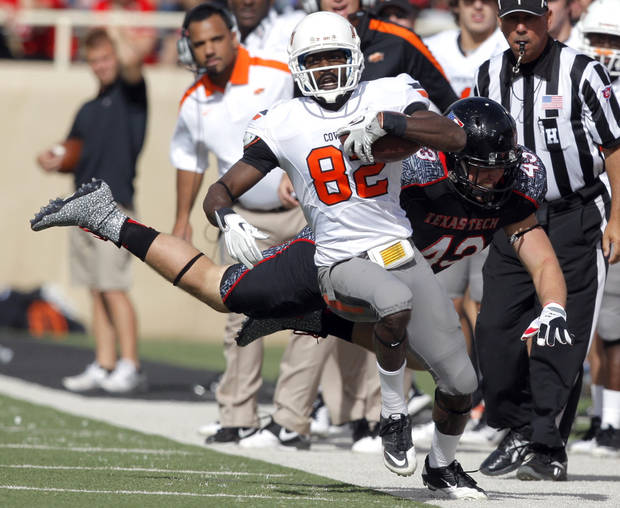 Oklahoma State's Isaiah Anderson (82) is forced out of bounds by Texas Tech's Daniel Cobb (42) during a college football game between Texas Tech University (TTU) and Oklahoma State University (OSU) at Jones AT&T Stadium in Lubbock, Texas, Saturday, Nov. 12, 2011.  Photo by Sarah Phipps, The Oklahoman  ORG XMIT: KOD