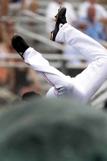 Miami Marlins third baseman Placido Polanco dives over a tarp but is unable to catch a foul ball hit by Washington Nationals' Bryce Harper during the third inning of an exhibition spring training baseball game Wednesday, March 20, 2013, in Jupiter, Fla. (AP Photo/Jeff Roberson)