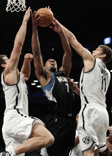Brooklyn Nets' Brook Lopez (11) and Kris Humphries (43) defend Minnesota Timberwolves' Derrick Williams (7) during the first half of an NBA basketball game, Monday, Nov. 5, 2012, in New York. (AP Photo/Frank Franklin II)