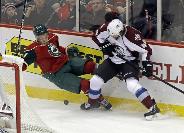 Minnesota Wild's Mikael Granlund of Finland, left, making his NHL debut, is upended by Colorado Avalanche's Ryan Wilson in a battle for the puck in the first period of an NHL hockey game Saturday, Jan. 19, 2013 in St. Paul, Minn.  (AP Photo/Jim Mone)