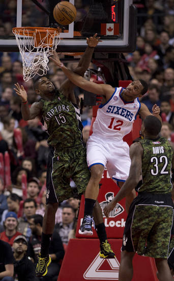 Toronto Raptors forward Amir Johnson, left, blocks Philadelphia 76ers forward Evan Turner who was on his way to the hoop during first-half NBA basketball action action in Toronto, Saturday, Nov. 10, 2012. (AP Photo/The Canadian Press, Frank Gunn)