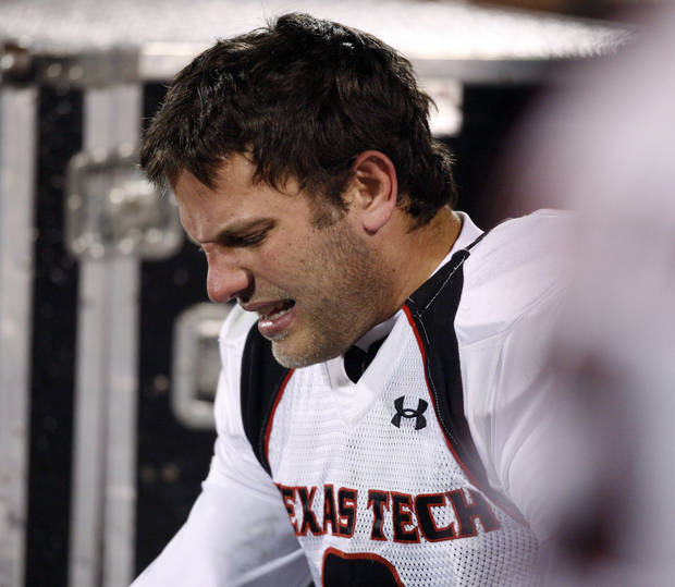 Texas Tech quarterback Graham Harrell grimaces as trainers work on a sore foot during the second half of the college football game between the University of Oklahoma Sooners and Texas Tech University at the Gaylord Family -- Oklahoma Memorial Stadium on Saturday, Nov. 22, 2008, in Norman, Okla.   BY STEVE SISNEY, THE OKLAHOMAN