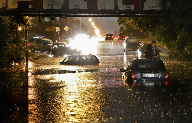 A man stands on top of his car as it is flooded on S. May Ave near SW 25th in Oklahoma City, Friday, May 31, 2013. Photo by Chris Landsberger, The Oklahoman.