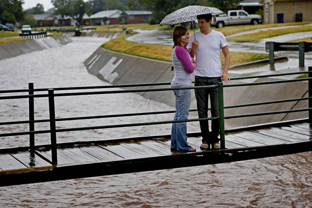 From under an umbrella Sarah Levy and Nathan Mickle watch water flow down a drain ditch in The Village, Okla., after a storm, Saturday, August 18, 2012. Photo by Bryan Terry, The Oklahoman