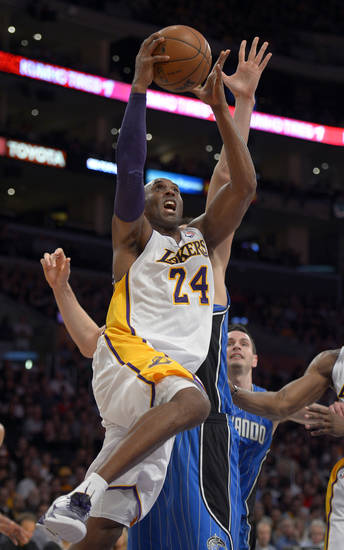 Los Angeles Lakers guard Kobe Bryant, left, puts up a shot as Orlando Magic center Nikola Vucevic, center, of Montenegro, and guard J.J. Redick defend during the first half of their NBA basketball game, Sunday, Dec. 2, 2012, in Los Angeles. (AP Photo/Mark J. Terrill)
