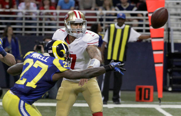 San Francisco 49ers quarterback Colin Kaepernick, right, tries to toss the ball to teammate Ted Ginn as St. Louis Rams' Quintin Mikell (27) defends during the second half of an NFL football game on Sunday, Dec. 2, 2012, in St. Louis. The play was ruled a fumble, recovered by Rams' Janoris Jenkins who took it in for a touchdown. (AP Photo/Seth Perlman) ORG XMIT: MOJR119