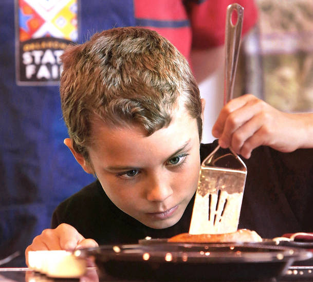 James McAffrey, 9, of Oklahoma City, prepares to flip his custom creation of Boston cream pie pancakes on Saturday while competing in the Shawnee Mills� Kids� Pancakes, Flapjacks and Griddle Cakes Contest at the Oklahoma State Fair.  PHOTOS BY JIM BECKEL, THE OKLAHOMAN