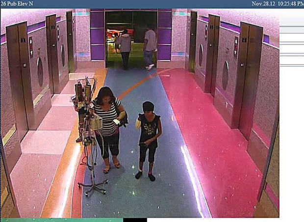 In this hospital surveillance photo released by the Phoenix Police Department on Monday, Dec. 3, 2012, a woman is seen with her 11-year-old daughter, a leukemia patient who had her arm amputated and a heart catheter inserted due to an infection. Authorities say the woman inexplicably took the girl from the hospital last week. Police say that if the catheter is left in too long it could lead to a deadly infection. The family�s identity is being withheld but they are calling the girl Emily. (AP Photo/Phoenix Police Department)
