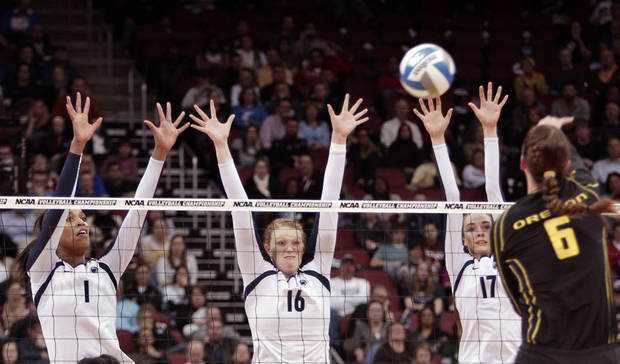 Oregon's Liz Brenner (6) hits over the triple block attempt by Penn State's Ariel Scott (1), Katie Slay (16) and Megan Courtney (17) during the national semifinals of the NCAA college women's volleyball tournament semifinal in Louisville, Ky., Thursday, Dec. 13, 2012.  (AP Photo/Garry Jones)