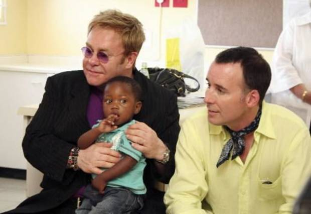 Elton John holds a baby he wanted to adopt with his partner David Furnish.  (AP photo by Johny Bergius)