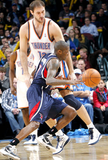 Atlanta's Jamal Crawford runs into Oklahoma City's Nenad Krstic   during their NBA basketball game at the OKC Arena in Oklahoma City on Friday, Dec. 31, 2010. Photo by John Clanton, The Oklahoman