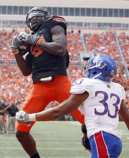 Oklahoma State's Justin Blackmon (81) scores a touchdown as Kansas' Tyler Patmon (33) defends during the first half of the college football game between the Oklahoma State University Cowboys (OSU) and the University of Kansas Jayhawks (KU) at Boone Pickens Stadium in Stillwater, Okla., Saturday, Oct. 8, 2011. Photo by Sarah Phipps, The Oklahoman