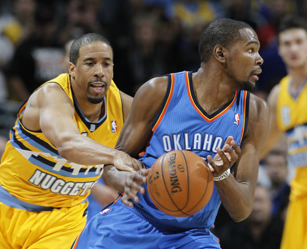 Denver Nuggets guard Andre Miller, left, reaches in for the ball and is called for a foul against Oklahoma City Thunder forward Kevin Durant in overtime of an NBA basketball game in Denver on Sunday, Jan. 20, 2013. The Nuggets won 121-118 in overtime. (AP Photo/David Zalubowski)