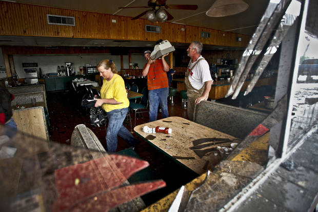 Seen through broken window glass employees gather valuables from the inside of the Anderson Travel Plaza after a tornado damaged the area around I-40 and Choctaw Road on Monday, May 10, 2010, in Oklahoma City, Okla.  Photo by Chris Landsberger, The Oklahoman