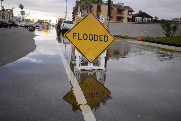 The Pacific Coastal Highway is partially flooded Wednesday morning, Dec. 13, 2012 in the Sunset Beach area of Huntington Beach, Calif. Astronomical high tides have caused minor street flooding in some low-lying areas along the Southern California coast. (AP Photo/The Daily Breeze, Sean Hiller)  MAGS OUT; NO SALES