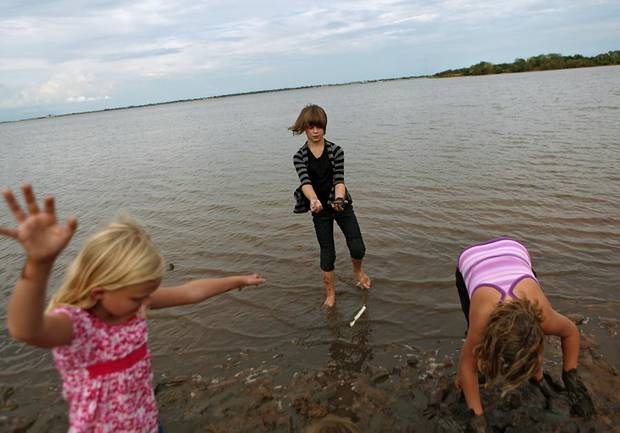 Liberty Samuels Amanda Matney and Sydney Beam (from left to right) play at Lake Hefner in Oklahoma City on Tuesday, Sept. 7, 2010. The girls collected clams and interestingly colored rocks and kept bait minnows alive in small pools they formed in the mud.  Photo by John Clanton, The Oklahoman